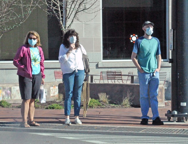 Masked shoppers wait for the crosswalk signal on Public Square in Wooster.