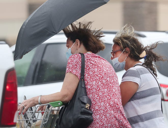 Shoppers brave high winds and strong rains on Monday as outer bands of Tropical Storm Eta swept the area.