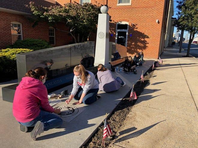 Members of the Greencastle-Antrim High School Art Club put fresh paint on the emblems at the Greencastle-Antrim Veterans Memorial on Nov. 4.