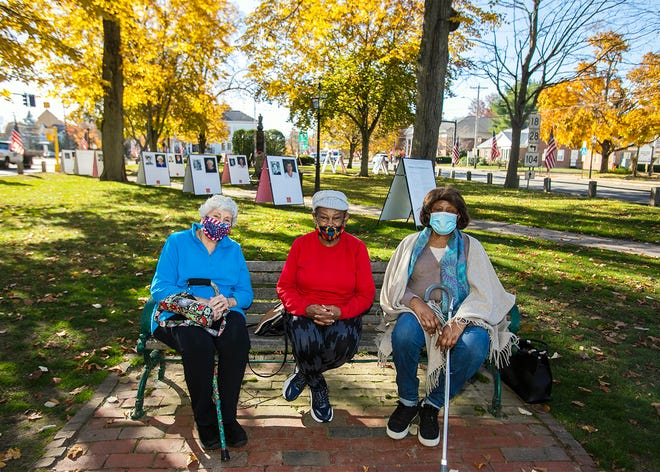 Bridgewater's Evelyn DeLutis, 78, Doris Campbell, 79, and Virginia Johnson, 80, smile for a photograph in the Bridgewater Town Commons on Monday, Nov. 9, 2020. Behind them are photographs, including portraits of themselves as teenagers and now, that are part of The Reunion Project, an exhibit made possible by Bridgewater State University students and the Bridgewater Council on Aging.