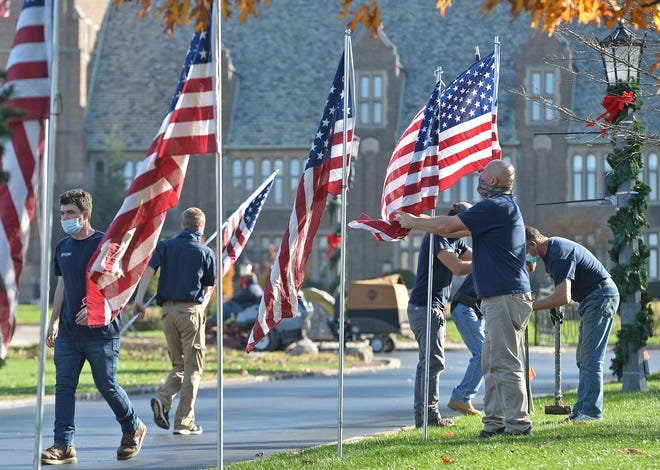 On Friday, in advance of Veterans Day, a grounds crew sets out some of the 50 flags lining the driveway entrance to Old Main at Mercyhurst University in Erie.