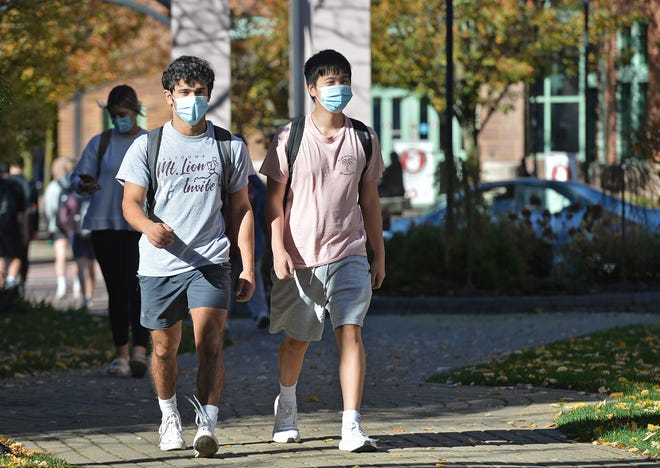 Gannon University freshmen Anthony Constantino, at left, and Ryan Phan, at right, walk along A.J.'s Way Monday at Gannon's downtown Erie campus. Wearing shorts and t-shirts, Constantino, 18, of Johnstown; and Phan, 19, of Sacramento, California, were dressed right for the record-high temperature in Erie, which was 79 degrees at 2:43 p.m.