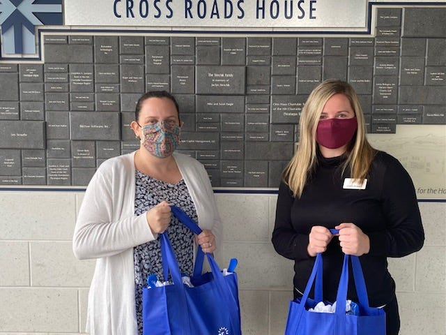 Jessica Parker of Crossroads House, left, and Caitlin Howard of Well Sense NH during a delivery of kits for the area's homeless population.