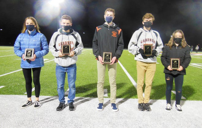 The Gardner High boys' and girls' cross country teams recently held their annual awards ceremony under the lights on the Watkins Field track. Participants were asked to wear masks or face coverings and social distance in accordance with COVID-19 guidelines. The season ended abruptly in late October, due to a rise in the number of COVID-19 cases in the city and in surrounding communities, with the girls' team finishing the shortened season undefeated at 4-0 and the boys' team finishing 3-1. Athletes receiving awards at the banquet were (from left to right): Olivia Powers, Coaches Award; Jack McDermott, Most Valuable Player Award; Alex Lucier, Top Newcomer Award; Noah Johnson, Most Improved Award; and Krista Bettez, Most Valuable Player Award.