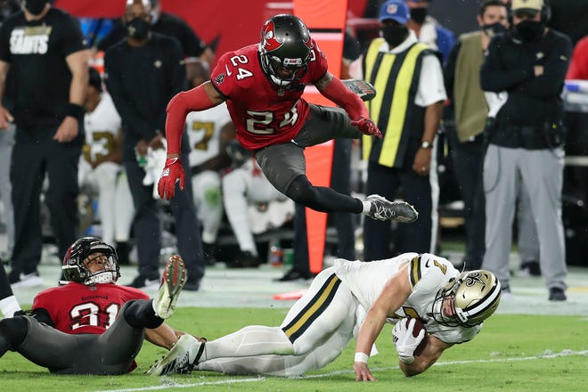 Tampa Bay cornerback Carlton Davis (24) flies through the air as he teams up with strong safety Antoine Winfield Jr. (31) to take down New Orleans Saints quarterback Taysom Hill (7) during the first half on Sunday night in Tampa.