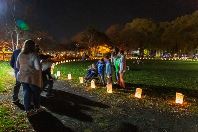 The family of Paul Eddinger gathers for a group photo alongside his luminaria at Kershaw Park.