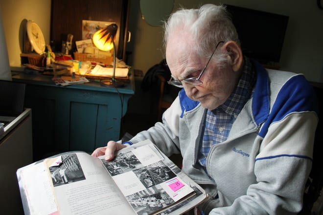 In his room at the M.M. Ewing Continuing Care Center, Carl Greene, who turns 100 on Nov. 10, thumbs through a book about supplying the troops during World War II. It is open to a page with a photo of an assembly line for bomb fuses, located in Canandaigua at a former garment factory.