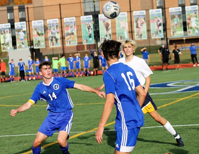Oyster River's Aidan Kelley (14) keeps his eye on the ball as teammate Andres Alcocer (16) and Bow's Zachary Anaderson move in during Saturday's Division II boys soccer championship game in Durham.