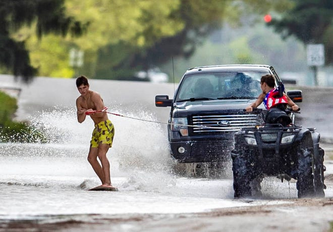 Benjamin Pfortner skimboards along 60th Street N as he is pulled by Bryson Hayden West of Coconut Boulevard in Loxahatchee. Palm Beach County schools were closed Monday due to Hurricane Eta so the Seminole Ridge High School students spent an hour surfing the flooded road, November 9, 2020. (ALLEN EYESTONE/THE PALM BEACH POST)