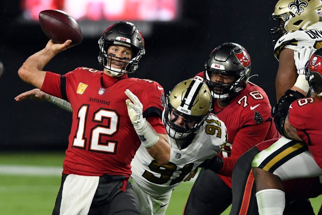 Tampa Bay Buccaneers quarterback Tom Brady (12) is pressured by New Orleans Saints defensive end Trey Hendrickson (91) as he throws a pass during the second half of an NFL football game Sunday, Nov. 8, 2020, in Tampa, Fla. (AP Photo/Jason Behnken)