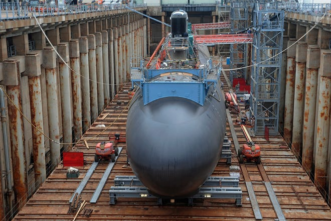 FILE- In this July 30, 2015, file photo, shipyard workers work at General Dynamics Electric Boat in Groton, Conn., prepare a submarine for float-off. Connecticut and Rhode Island officials are celebrating a new submarine contract for General Dynamics Electric Boat as a major economic win for the region's economy. The $9.47 billion contract with the U.S. Navy, which was announced Friday, Nov. 6, 2020, is for construction and testing of the first two Columbia-class submarines.  AP Photo/Jessica Hill, File)