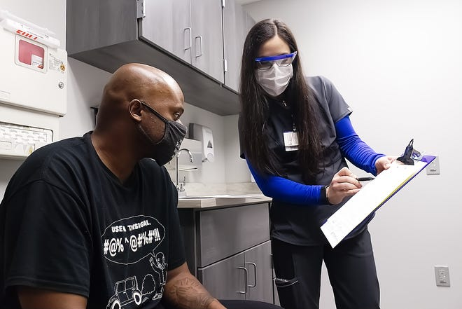 Crystal Clinic Athletic Trainer Natalie Dragovich goes over some paperwork with Shawn Boyd, of Tallmadge, who was at the new QuickCare clinic in Franklin Township at the corner of routes 59 and 261.