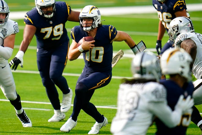 Los Angeles Chargers quarterback Justin Herbert, center, runs with the ball during the first half of an NFL football game against the Las Vegas Raiders, Sunday, Nov. 8, 2020, in Inglewood, Calif. (AP Photo/Alex Gallardo)