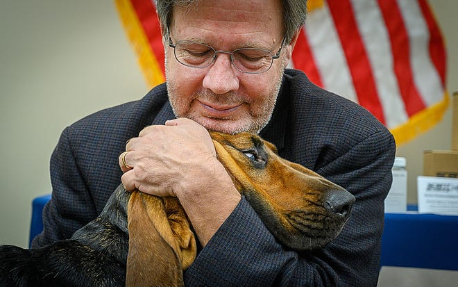 State Rep. Scott Plakon, whose wife, Susie, suffered from early onset Alzheimer's before she died at 57, hugs a St. Johns County Sheriff's Office bloodhound called Daisy at the Sheriff's Office complex in St. Augustine on Monday. Daisy got her name to honor Susie, whose favorite flower was the daisy.