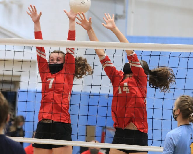 Leaping to block a shot for the Smyrna High School volleyball team are Karalyn Osborne (left) and Anna Richardson.