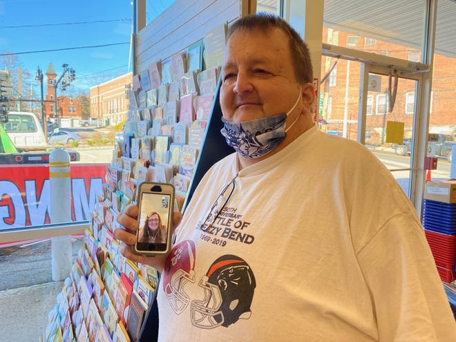Everett A. Blodgett Jr. stands near the $1 greeting cards while video calling his daughter, Casey Osei-Bonsu. The father-daughter team will soon open the DP Dollar Plus store on Main Street.