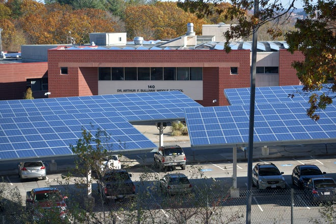 Solar panels are visible on the top of a car port in the parking lot of the Dr. Arthur F. Sullivan middle school in Worcester. Environmentalists are advocating for similar solar installations on already developed sites including parking lots and rooftops rather than continued deforestation for solar arrays.