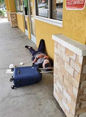 A homeless person sleeps outside Your CBD Store Gainesville.