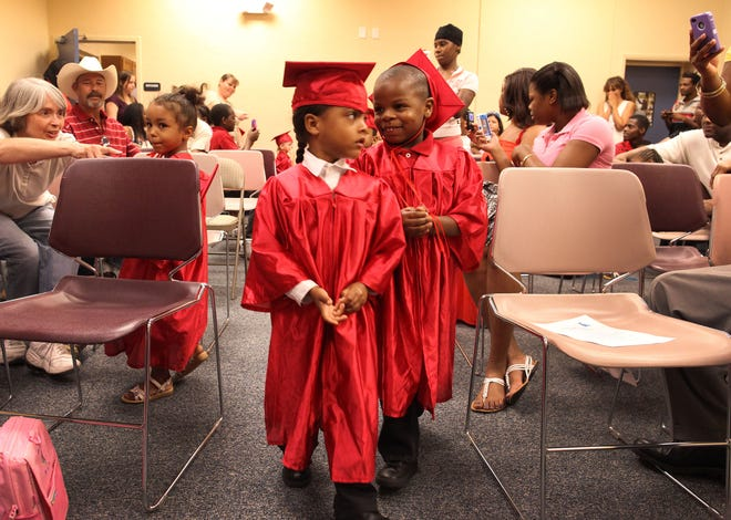 Two 4-year-old children walk during a graduation ceremony for parents and kids who participated in the Healthy Families Florida program at the Library Partnership in 2011.