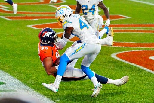 Denver Broncos tight end Albert Okwuegbunam (85) scores a touchdown as Los Angeles Chargers cornerback Michael Davis (43) defends during the second half of an NFL football game, Sunday, Nov. 1, 2020, in Denver.