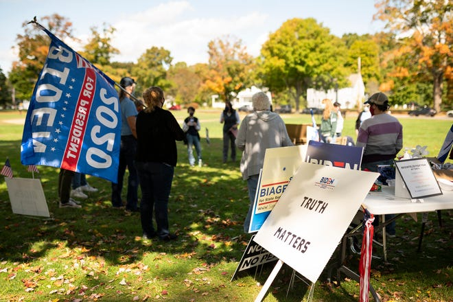 Supporters of Joe Biden gather Oct.3 on the West Brookfield town common as a roll rally for President Donald Trump passes through on it's way to Leicester.