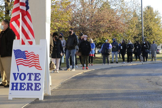 Socially distanced voters wait in line for the polls to open Tuesday at the Celebration Ministry Center of Faith Lutheran Church in Appleton.