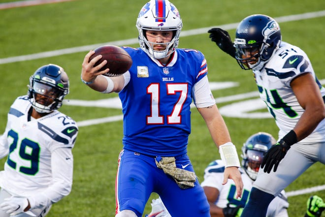 Buffalo Bills quarterback Josh Allen (17) rushes past Seattle Seahawks' Bruce Irvin (51) and Jayson Stanley (29) for a touchdown during the second half of an NFL football game Sunday, Nov. 8, 2020, in Orchard Park, N.Y. (AP Photo/Jeffrey T. Barnes)