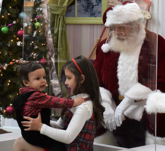 Camila Tirado, 8, holds her year-old brother Luis on her lap during a visit with Santa Clause Friday at Cherry Hill Mall.