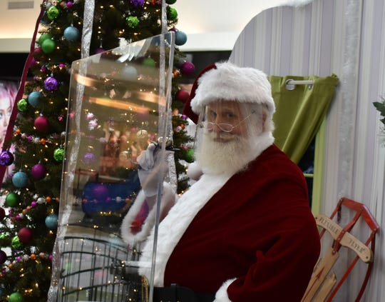 Santa Claus is wearing a face mask and is positioned behind a plexiglass shield as precautions against the spread of COVID-19 at Cherry Hill Mall.