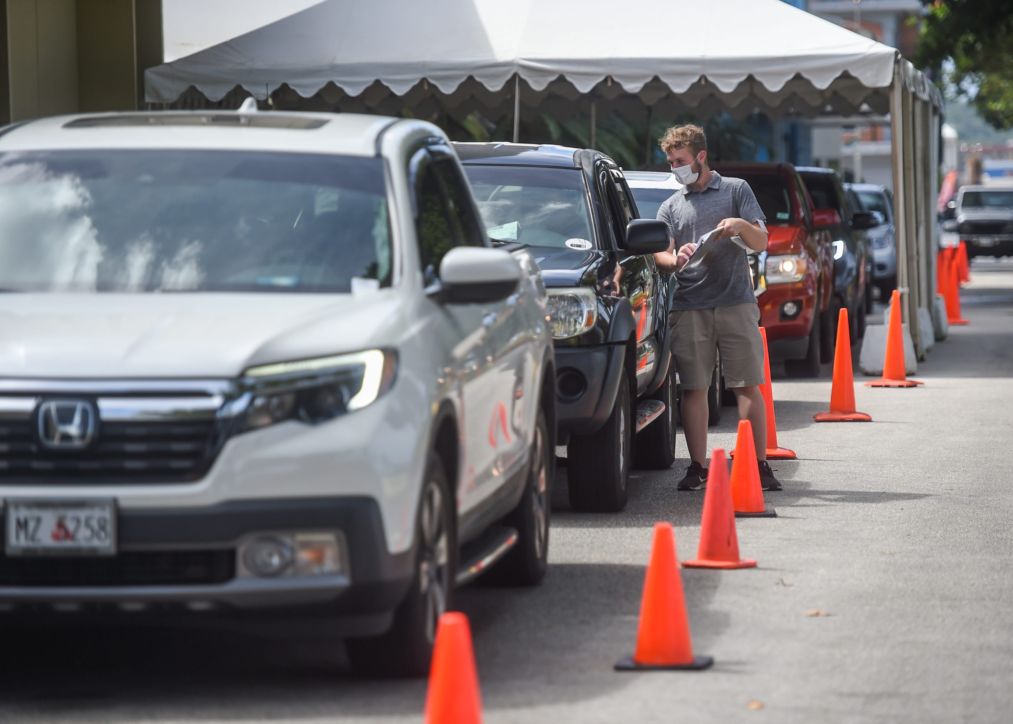 Guam Election Commission employees assist early voters of the 2020 Runoff Election at their curbside voting drive-thru in Hagåtña, Monday.