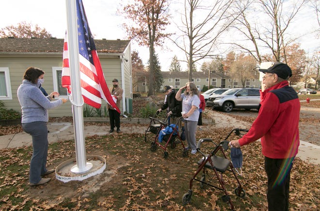 As Mill Pond Manor Apartments Community Manager Julie Jaworski raises the American flag on the newly-installed flagpole in Brighton Monday, Nov. 9, 2020, veterans, from left, Don Berry, U.S. Navy, Vietnam War, Billy Riecker, U.S. Navy, World War II, Kathryn Reyes, U.S. Navy, Vietnam War and Paul Moskal, U.S. Air Force pay respect to the raising of the flag. Not shown is veteran and resident Mark Demsky of the U.S. Air Force.