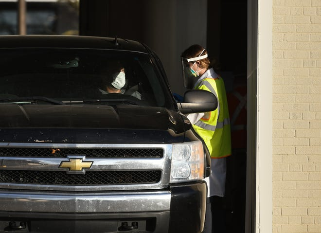 A man in a truck seen at Sparrow Healthcare's drive thru COVID-19 testing services, pictured Monday, Nov. 9, 2020, in Lansing.