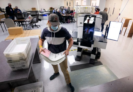 Maricopa County Elections Department employee Charles Cooley tabulates ballots at county elections headquarters in Phoenix on Nov. 9, 2020.