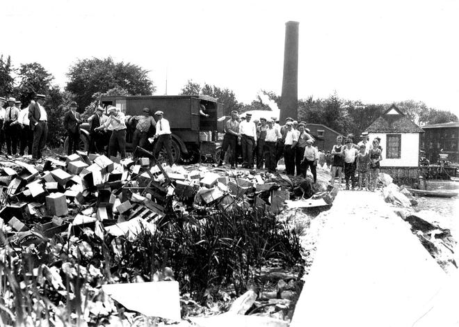 This Prohibition-era photo from the Ottawa County Museum's archives shows a crowd gathering at Waterworks Park to watch local authorities destroy confiscated illegal liquor.