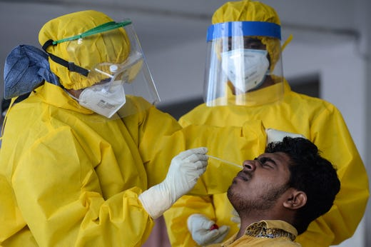 Medical workers collect a swab sample from a resident to test for the COVID-19 coronavirus in Colombo on Nov. 9, 2020.