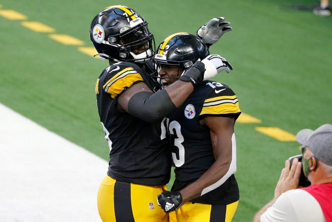 Offensive lineman Chukwuma Okorafor and receiver James Washington celebrate Washington's first-half touchdown in the Steelers' 24-19 victory over the Dallas Cowboys Sunday.