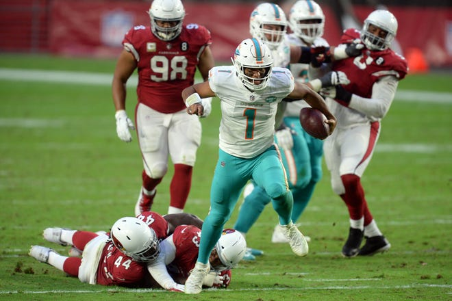 Dolphins quarterback Tua Tagovailoa eludes Cardinals linebacker Markus Golden and cornerback Byron Murphy in Sunday's 34-31 win in Arizona.