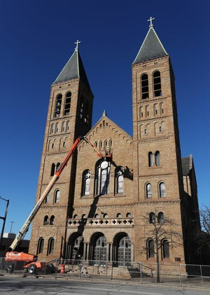 Shane Nickol and Timothy Farmer of Warren Roofing use a lift to work on St. Bernard Catholic Church in downtown Akron on Tuesday. St. Bernard Parish hopes to raise $1.5 million to pay for the restoration of the 115-year-old building.