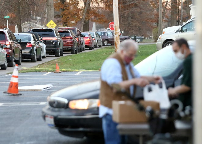 A line of cars snakes around St. Ann Catholic Church in Sebring during a curbside dinner giveaway on Monday.