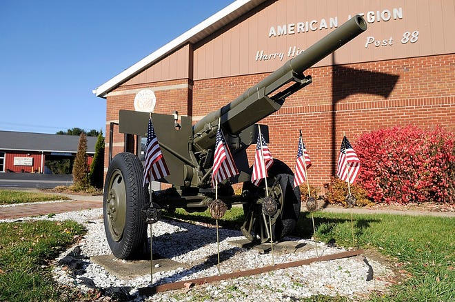 American flags are placed around the gun outside the Harry Higgins American Legion Post 88 for the Veterans Day ceremony on Wednesday.