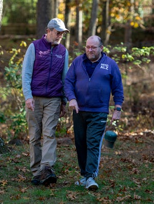 Tim Weaver, left, and Phil Gutis take a walk around their property in New Hope, on Monday. Gutis was diagnosed with Alzheimer's five years ago and is taking part in an experimental trial.