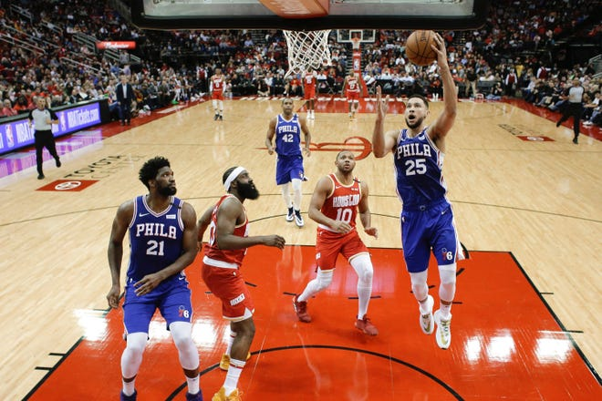 The Sixers' Ben Simmons drives to the basket as teammate Joel Embiid and the Rockets' James Harden, 13, watch.