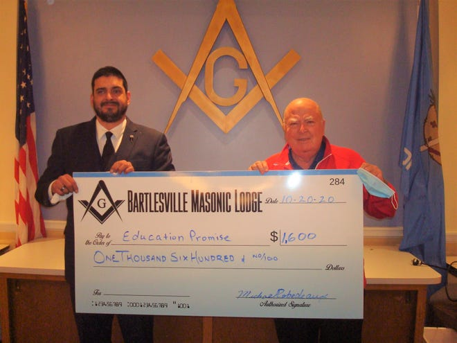 Michael Robedeaux of Bartlesville Masonic Lodge, left, presents a check to Martin Garber of Education Promise. The Bartlesville Masonic Lodge recently donated a total of  $13,600 to a number of local charities, including The Bartlesville Police Foundation, Family Promise, The Kiddie Park, Washington County SPCA, and Jane Phillips Wellness Scholarships.