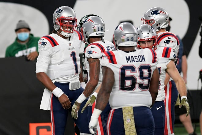 New England Patriots quarterback Cam Newton, left, celebrates a touchdown against the New York Jets on Monday night.
