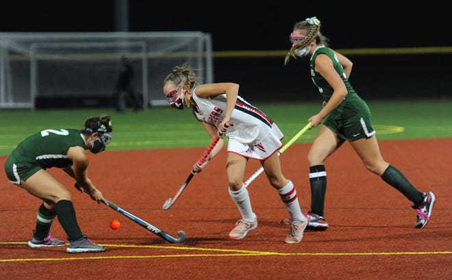 D-Y's Grace Cotoia, left, tries to block a play by Barnstable's Reagan Hicks in the first round of the Cape & Islands League Atlantic field hockey tournament on Monday. [Merrily Cassidy/Cape Cod Times]
