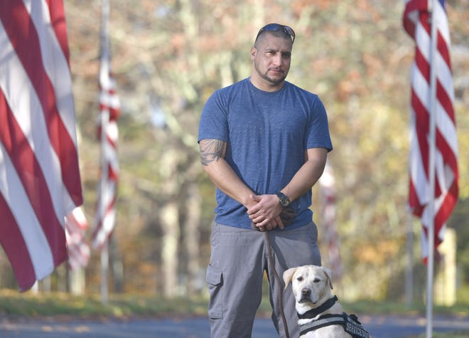Iraq War veteran Anthony Encarnacion stands with his service dog, Aces, at the entrance to the Massachusetts National Cemetery in Bourne. Encarnacion, 34, struggled with substance abuse and homelessness when he returned to the Cape after his deployment overseas.