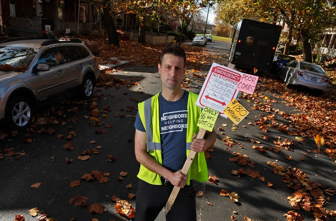 Chet Ridenour on Tuesday holds a protest sign he created speaking up for neighbors who have been unnecessarily affected by the recent repaving project on Wilber Avenue in Columbus. He wants the city to refund ticket and impoundment fees to owners of cars towed during the paving project.