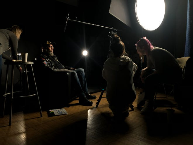 """Columbus College of Art & Design student filmmakers, from right, Madison Van Buren and Madeline Anson, work with CCAD faculty Stephanie West to set up for their shoot with veteran Leni D. Anderson for a documentary that premieres Nov. 13, """"Re-story: Transforming Veteran Stories into Art."""""""