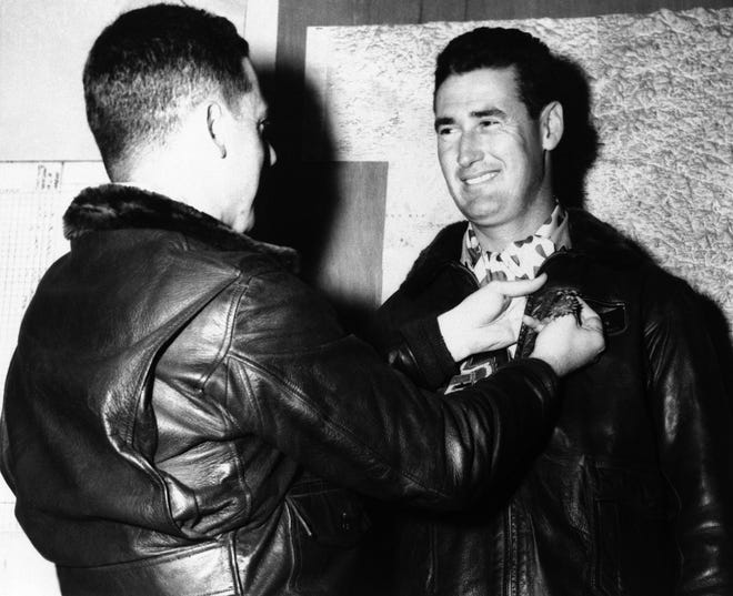 """Baseball hall of famer and U.S. Marine Corps Captain Ted Williams, is presented the Air Medal and two Gold Stars in lieu of the second and third air medals, by Lieut. Col. Bernard McShane, commanding officer of the """"Panther Jet"""" squadron, at a forward air base of the First Marine Aircraft Wing in Korea, July 15, 1953. [AP]"""