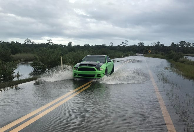 A car navigates flooded roads on the Scenic Loop in Ormond Beach on Tuesday, Nov. 10, 2020